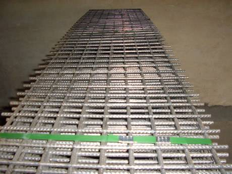 Many rectangular sheets of reinforcement welded mesh are packed with green baling strip.