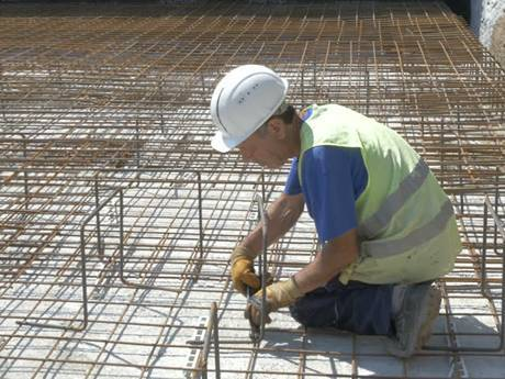 An elderly worker is using pliers to reinforce the mesh on the building floor.