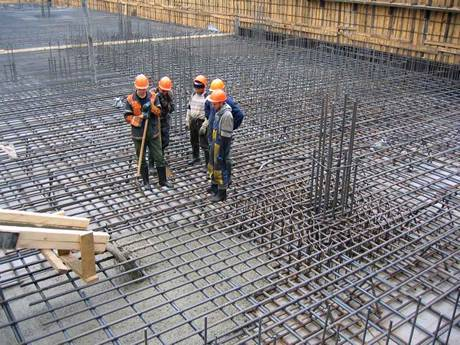 Five workers are standing on the foundation of concrete reinforcing mesh.