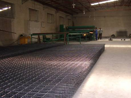 Many pieces of reinforcement welded mesh are in workshop. Beside the mesh, there is a welding machine and two workers.