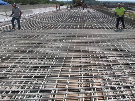 Some workers incorporate the concrete reinforcing mesh to the road.