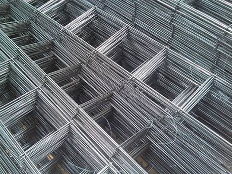 Many galvanized ladder mesh reinforcements are placed on the ground.