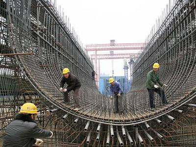 Several workers are using concrete reinforcing mesh to build a curved bridge.