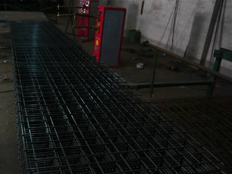 Many sheets of black galvanized concrete reinforcing mesh are placed in the workshop.