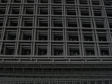 Many pieces of black galvanized welded mesh with square openings are placed together.