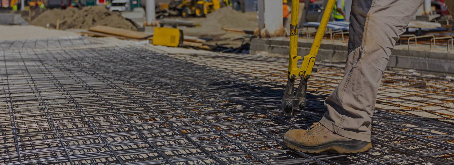 Concrete reinforcing mesh placed on the ground, and a worker uses pliers with two long yellow arms to fasten the mesh.