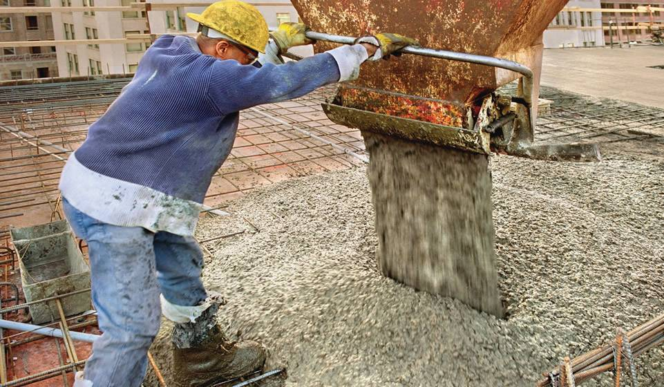 Reinforcing welded concrete mesh placed on the road surface, and a worker is using the machine to pour the concrete.